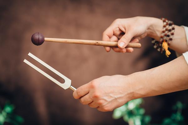 Emberi kézben egy óriás hangvilla és egy hangtálakhoz használatos puha dobverő.