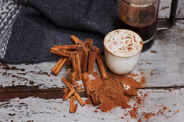 Fahéjjal megszórt tejhabos kávé, mellette fahéjrudak és sok-sok fahéjpor.