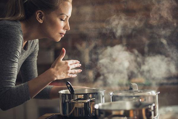 Fazékban fővő levest illatoz konyhájában egy hölgy.