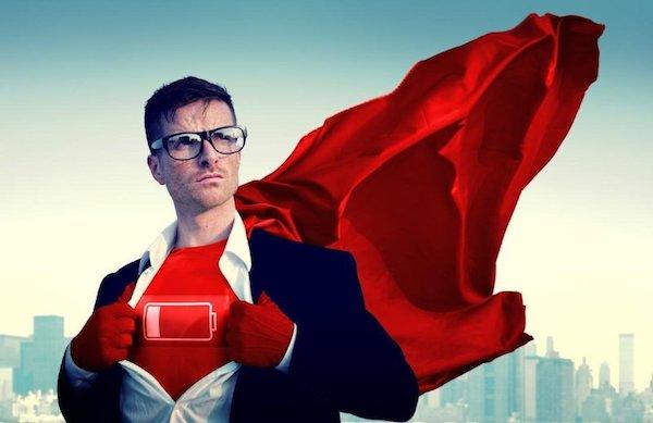 Superman jelmezbe öltözött férfi piros pólóján egy elemerült elem ikon van.