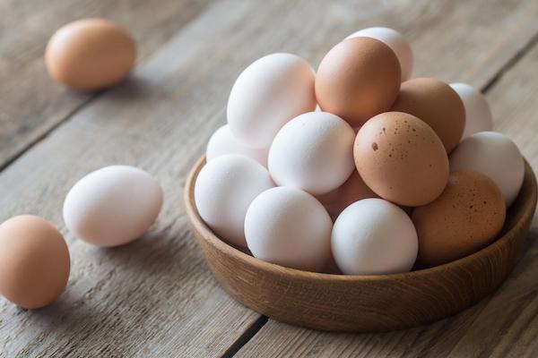 Különféle színű tojások egy lapos bambusztálban.