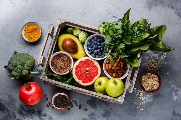 Egészséges táplálékok egy fatálcán: zöldalma, grépfrút, avokádó, áfonya, mandula, kurkuma, fűszernövények, zab, gránátalma, brokkoli, kelbimbó, paprika.