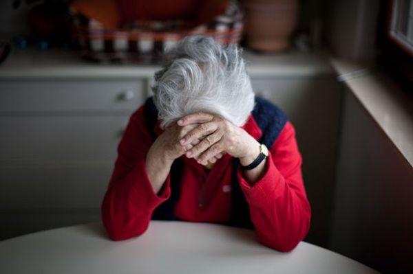 Idős néni támasztja a fejét a konyhaasztalnál.