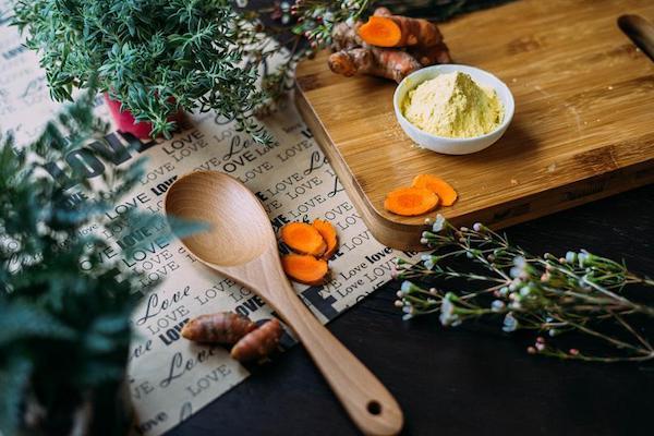 Asztalon különféle gyógynövények: kurkumagyökér, porított gyömbér és rozmaring cserépben.