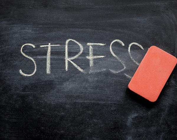 Stressz szó letörlése piros szivaccsal egy fekete tábláról.