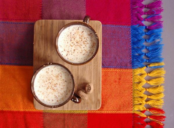 Meleg tejbe csipet szerecsendió felülről fotózva két pohárban, színes terítővel.