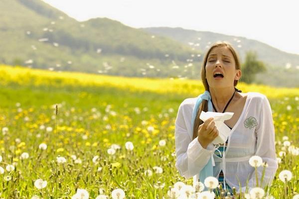 Pitypangokkal teli réten tüsszögő fiatal nő.