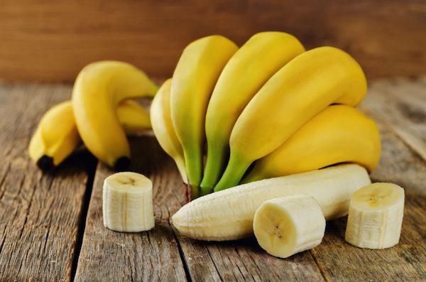 Egy fürt banán, mellette egy gyümölcs nagyobb szeletekre vágva.