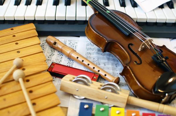Különféle hangszerek egymás mellett: szintetizátor, hegedű, furulya, xilofon, csörgők és kotta.