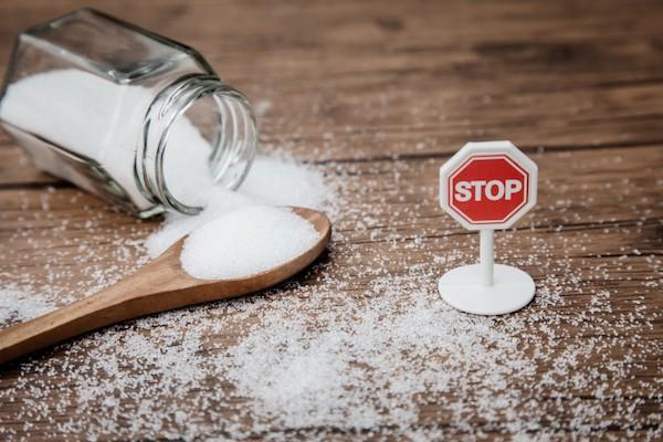 Üveg tartóból kiboruló cukor, fakanál és egy STOP tábla az asztalon.