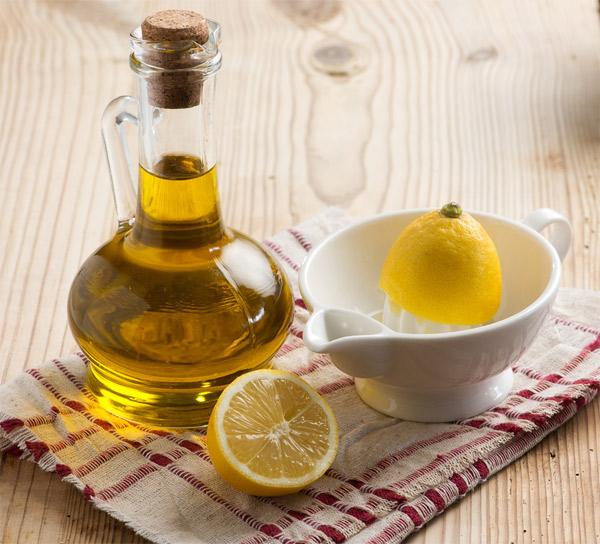 Olívaolaj kis kancsóban, mellette félbevágott citrom és citromcsavaró.