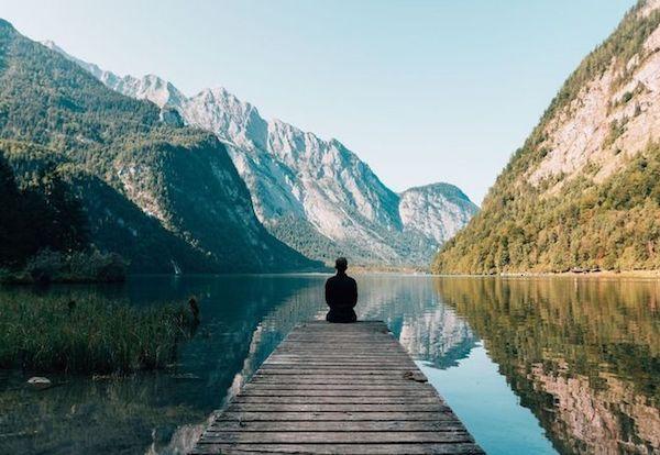 Gyönyörű hegyi tó mólóján magányosan ül egy férfi.