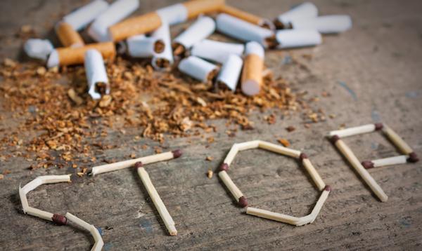 Dohányzásról való leszokást hirdető plakát képe: összetört cigarettadarabokkal és gyufaszálakból kirakott STOP szóval.