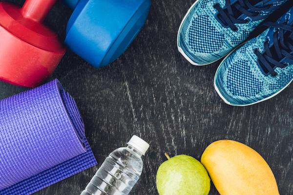Életmódváltás image képe: súlyzó, edzőcipő, gyümölcsök, ásványvíz.