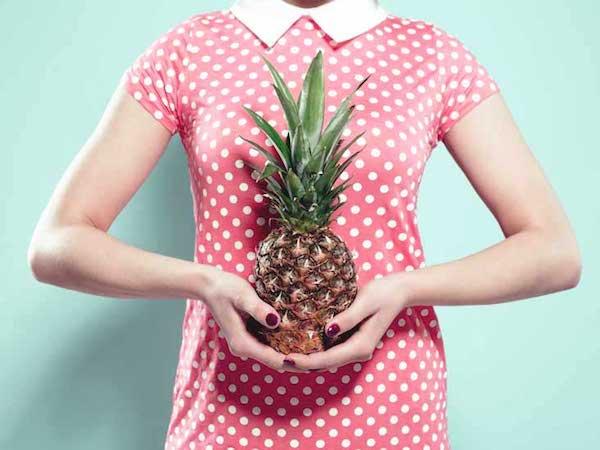 Pöttyös ruhában lévő hölgy egy ananászt tart a kezében.