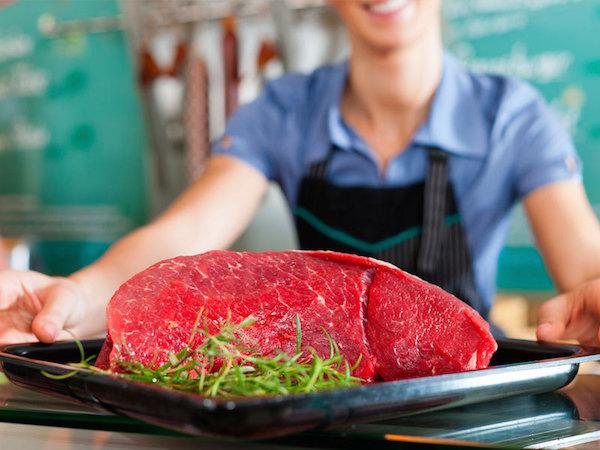 Tálcán kínál egy eladó egy jó adag nyers húst rozmaringággal.