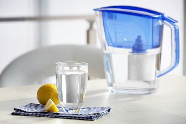 Vízszűrő kancsó, előtte egy pohár tiszta víz, mellette citrom.