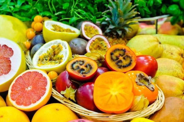 Különféle egzotikus gyümölcsök egészben és felezve egymás mellett.