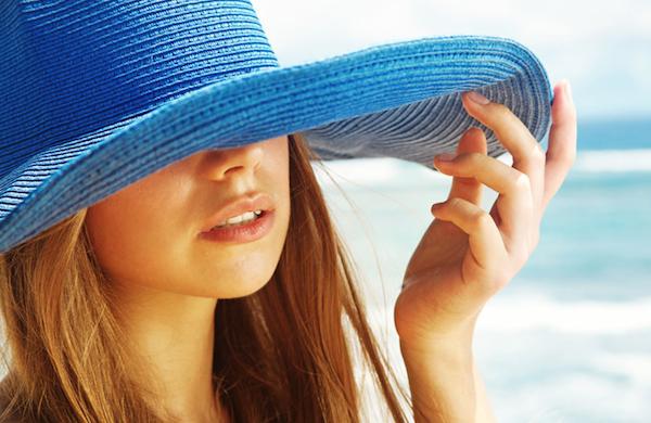 Kék szalmakalapban egy hosszú hajú hölgy.