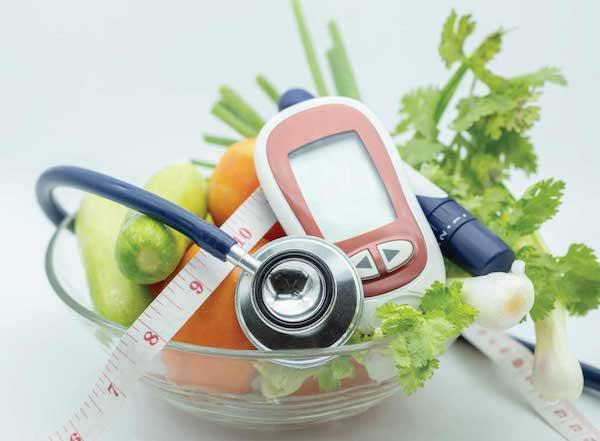Zöldségek és gyümölcsök egy tálban, mellettük cukorszintmérő, centiméter és fonendoszkóp.