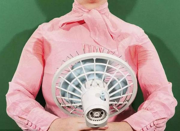 Hőhullámmal küszködő hölgy átizzadt selyemblúzában, kezében egy mini ventillátorral, melyet magára irányít.