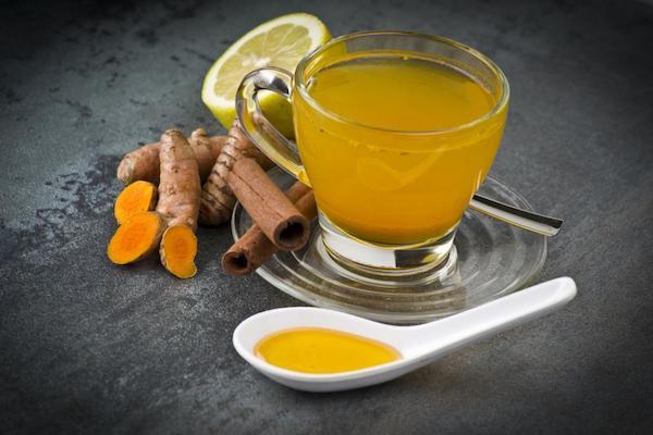 Kurkumatea kis csészében, mellette kurkma, fahéj és egy kanálban méz.