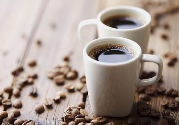 Két csésze frissen lefőzött kávé, mellette kávészemek.