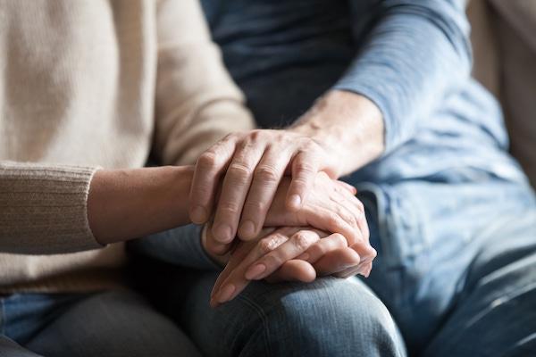 Idősebb férfi támogatón átfogja felesége kezét, melyet a térdén pihentet.