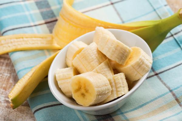 Banán felkarikázva egy kicsi tálban, mellette a lehúzott banánhéj.