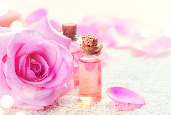 Rózsaszínű rózsa, mellette kis üvegben rózsaolaj.