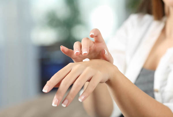 Ápolt kezét krémezi egy hölgy.