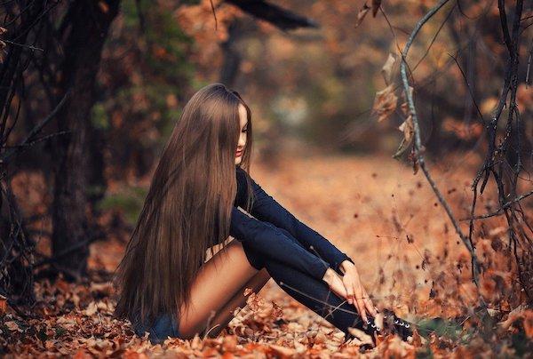 Hosszú hajú, csinos lány ül az avarban.