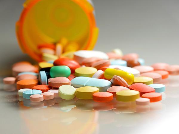 Különféle színű vitaminok kiöntve egy gyógyszeres üvegből.
