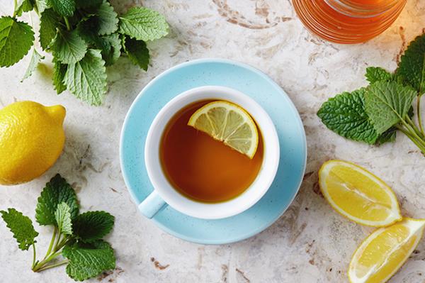 Citromfűtea egy fél szelet citrommal, mellette citromfűágak.