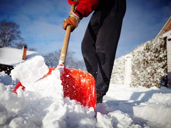 Egy férfi kesztyűben havat lapátol.