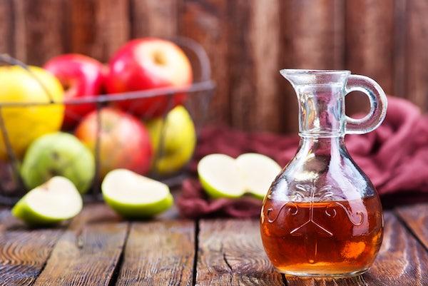 Különféle színű almák és a belőle készült almaecet díszes üvegben.