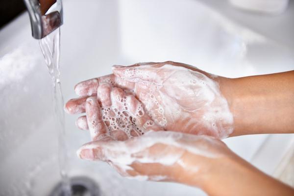 Beszappanozott kezét mossa valaki a mosdókagylónál.