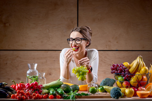 Fiatal lány egy gyümölcsökkel, töldségekkel teli asztal előtt szőlőt csemegézik.