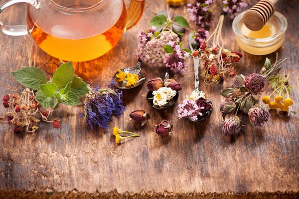 Rusztikus asztallapon különféle gyógynövények színes virágai egymás mellett, egy nagy kancsóban gyógynövénytea.