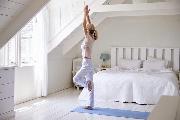 Fapóz gyakorlása az ablak előtt egy jógaszőnyegen a hálószobában.