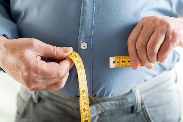 Egy férfi méri haskörfogatát centiméterrel.