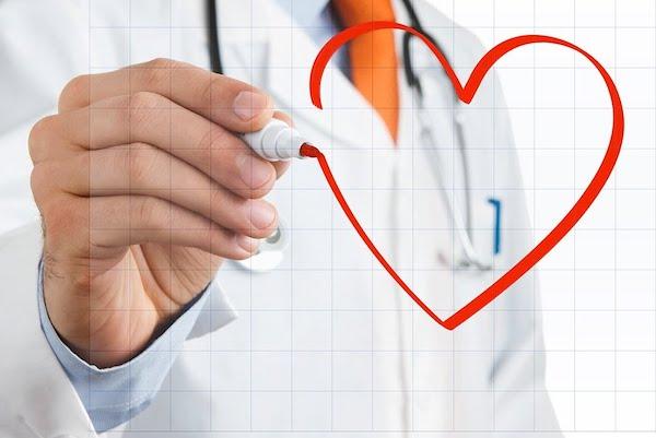 Piros tollal rajzol egy szívet egy orvos egy képzeletbeli táblára.