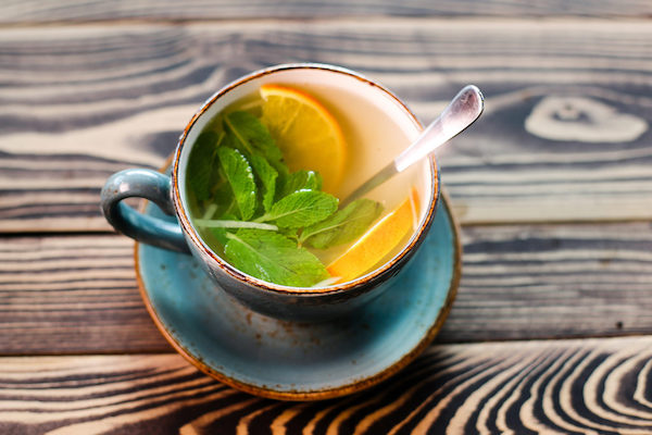 Citromfűtea csészében, benne citromfűlevelek és narancsszeletkék.