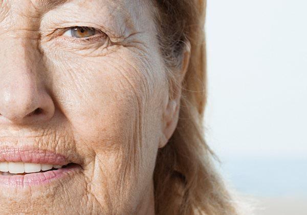 Idősebb, ráncos arcbőrű nő közeli arcfotója.