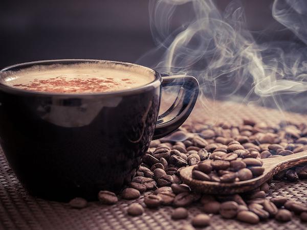 Gőzölgő, forró kávé, mellette kávészemek.