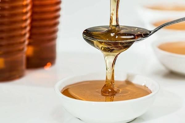 Mézet csorgatnak egy kanálon keresztül egy kisebb tálba.