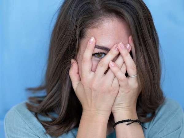 Fiatal nő kukucskál ki mosolyogva a kezei közül.