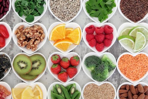Szív alakú tálkákban különféle egészséges táplálékok: gyümölcsök, magvak, saláták.