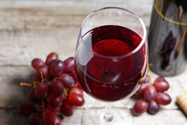 Egy pohár vörösbor, mellette szőlő és a borosüveg.