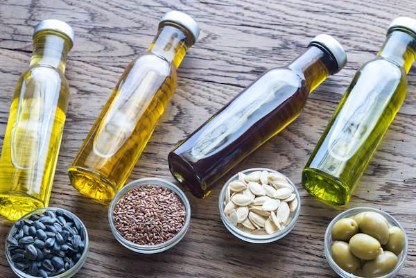 Különféle növényi olajaak egymás mellett (napraforgóolaj, lenmagolaj, tökmagolaj és olívaolaj).